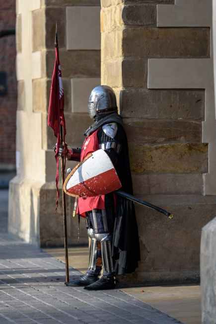 man wearing gray and red armour standing on the streets