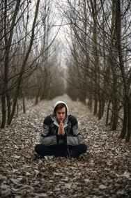man wearing gray black zip hoodie jacket praying in between black tree during daytime