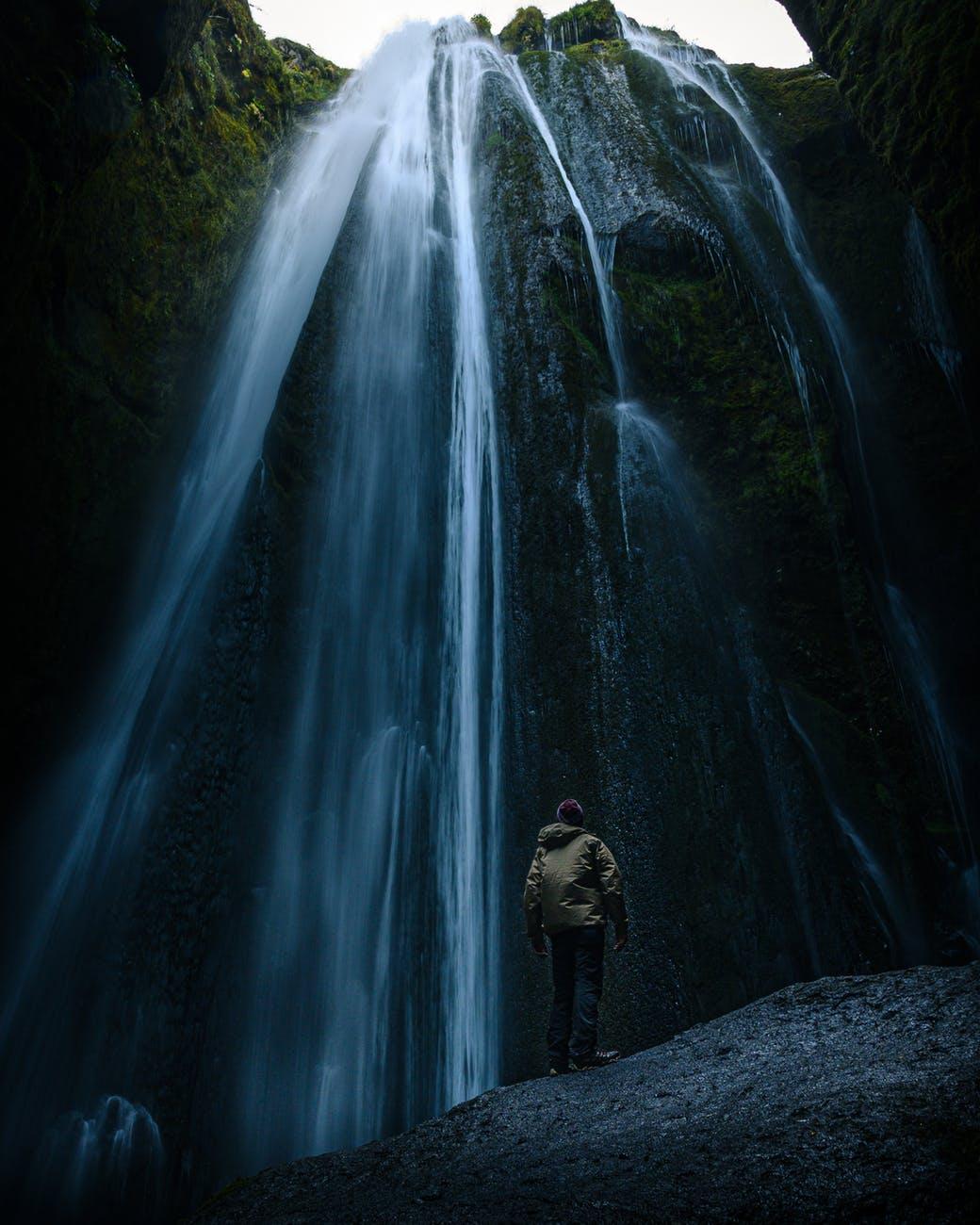 photo of man standing near the waterfalls